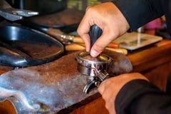 Pisón del barista de la mano que presiona el café del polvo en amoladora fotos de archivo libres de regalías