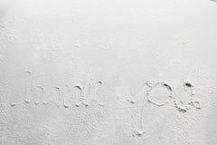 Pisać «Dziękuje ciebie! «na białej desce z pszeniczną mąką na powierzchni zdjęcia royalty free