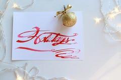 Pisać list kartę z tekstów wakacjami w szkarłatnym kolorze na białym shee Obrazy Royalty Free
