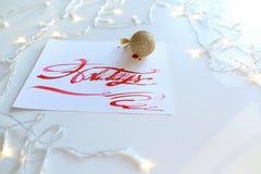 Pisać list kartę z tekstów wakacjami w szkarłatnym kolorze na białym shee Obrazy Stock