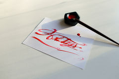 Pisać list kartę z tekstów wakacjami w szkarłatnym kolorze na białym shee Zdjęcie Stock