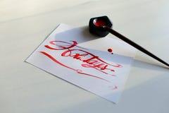 Pisać list kartę z tekstów wakacjami w szkarłatnym kolorze na białym shee Zdjęcia Royalty Free