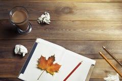 Pisać lub freelance praca stół Opróżnia otwartego notatnika z ołówkami i jesień liściem Wark kakaowa szklana filiżanka drewniany  zdjęcia stock