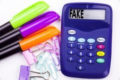 Pisać słowu Sfałszowanym wiadomość tekscie w biurze z otoczeniami tak jak markier na kalkulatorze, pióra writing Biznesowy pojęci zdjęcie royalty free