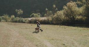 Pisać trzy lat chłopiec i bawić się z jego małym husky słonecznym dniem obok jeziora i psem zdjęcie wideo