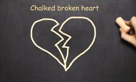 Pisał kredą złamane serce Inskrypcja na blackboard obraz stock