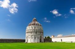 Pisa Baptistery Battistero di Pisa on Piazza del Miracoli Duomo square green grass lawn, city wall, Camposanto cemetery royalty free stock photo