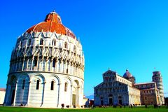 PISA, ITALY - CIRCA FEBRUARY 2018: The Baptistery, Pisa Cathedral and the Leaning Tower at the Square of Miracles royalty free stock image