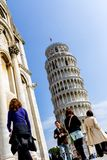 Pisa, Italy - March 17, 2012: People walking near the Tower of Pisa Torre di Pisa. It`s a freestanding bell tower of the royalty free stock photo