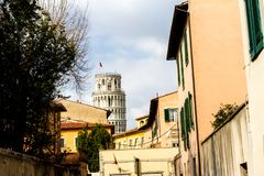 Pisa, Italy - March 17, 2012: Tower of Pisa is visible above street roofs. Torre di Pisa is a freestanding bell tower of the stock photos