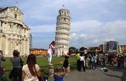 Tourists pose at the tower of Pisa, Italy Royalty Free Stock Photos