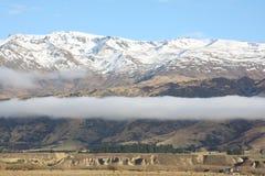 Pisa Mountain Range New Zealand. Fog sits beneath the peaks of Pisa Range New Zealand Royalty Free Stock Image
