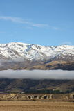 Pisa Mountain Range New Zealand. Fog sits beneath the peaks of Pisa Range New Zealand Stock Images