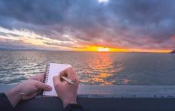 Pisać na notatniku przy zmierzchem Zdjęcie Royalty Free