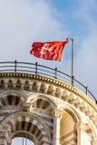 Pisa torndetalj - uppvisning av det bästa takområdet med den röda flaggan 2 royaltyfria bilder