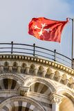 Pisa tower detail - showing the top roof area with the red flag. And arcs in detail Stock Images