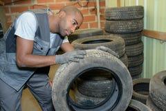 Pisada de examen del hombre en el neumático desmontado fotografía de archivo libre de regalías