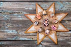Pisanky和种族星框架在木背景 在一张木表的复活节彩蛋 被绘的鸡蛋复活节假日 库存照片
