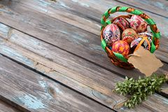 Pisanky in a wicker basket with green branch on a wooden background. Easter eggs on a wooden table. A busket with royalty free stock photos