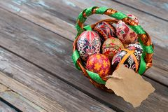 Pisanky in a wicker basket on a wooden background. Easter eggs on a wooden table. A busket with holiday eggs and blank stock images