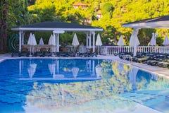 Piscina all'hotel con la barra Hotel vuoto, palme, ombrelli Fotografie Stock Libere da Diritti