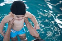 Piscina asiatica di lezioni del bambino e del padre in acqua fotografia stock