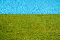 Piscina azul al lado del césped verde Fotos de archivo