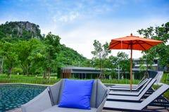 Piscina azul com cama e guarda-chuva imagens de stock royalty free