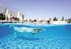 Piscina azul del día soleado de la mujer de la muchacha del vestido de la nadada subacuática blanca hermosa del salto Fotografía de archivo