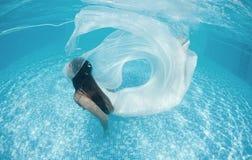 Piscina azul del día soleado de la mujer de la muchacha del vestido de la nadada subacuática blanca hermosa del salto Foto de archivo libre de regalías