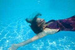 Piscina azul del día soleado de la mujer de la muchacha del vestido de la nadada subacuática hermosa del salto Fotografía de archivo libre de regalías