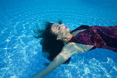 Piscina azul del día soleado de la mujer de la muchacha del vestido de la nadada subacuática hermosa del salto Fotografía de archivo
