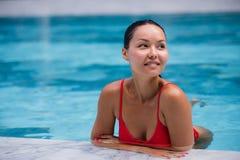 Piscina bonita da mulher do sorriso feliz asiático novo relaxado da menina do retrato do recurso em férias tropicais fotografia de stock royalty free