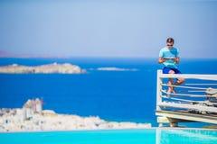 Piscina cercana relajante del hombre joven con el libro asombroso de la visión y de lectura en Grecia Fondo famoso hermoso Fotos de archivo