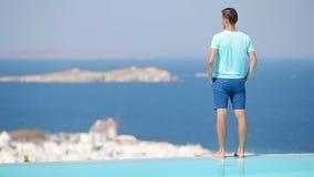 Piscina cercana relajante del muchacho joven con la opinión asombrosa sobre Mykonos, Grecia Fondo famoso hermoso almacen de metraje de vídeo