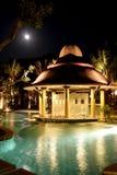 Piscina, chaise-lounge del sole vicino al giardino sotto la luna nel cielo notturno Immagine Stock