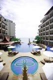 Piscina, chaise-lounge del sole Vista del mare, pagoda, cielo blu Immagine Stock