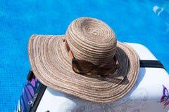 Piscina com água clara Mala de viagem, chapéu e vidros Fotos de Stock