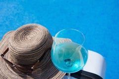 Piscina com água clara Mala de viagem, chapéu e vidros Foto de Stock Royalty Free