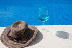 Piscina com água clara Mala de viagem, chapéu e vidros Imagens de Stock Royalty Free