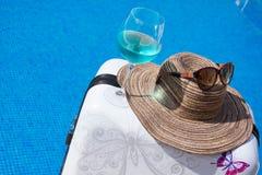 Piscina com água clara Mala de viagem, chapéu e vidros Fotografia de Stock