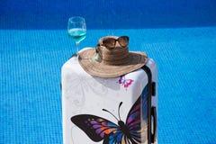 Piscina com água clara Mala de viagem, chapéu e vidros Foto de Stock