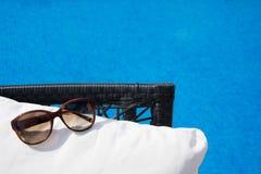 Piscina com água clara Mala de viagem, chapéu e vidros Imagens de Stock