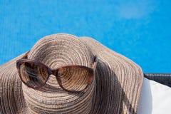 Piscina com água clara Mala de viagem, chapéu e vidros Imagem de Stock Royalty Free
