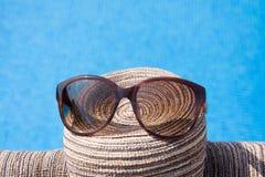 Piscina com água clara Mala de viagem, chapéu e vidros Imagem de Stock