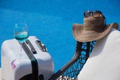 Piscina com água clara Mala de viagem, chapéu e vidros Fotografia de Stock Royalty Free