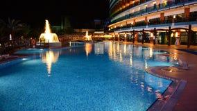 A piscina com as fontes na iluminação da noite