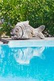 Piscina com escultura cinzelada de madeira dos peixes Imagem de Stock