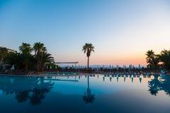 Piscina con las palmeras en la puesta del sol Reflexión del agua imagenes de archivo
