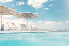 Piscina con las sillas de cubierta, paraguas, cielo Imagen de archivo libre de regalías